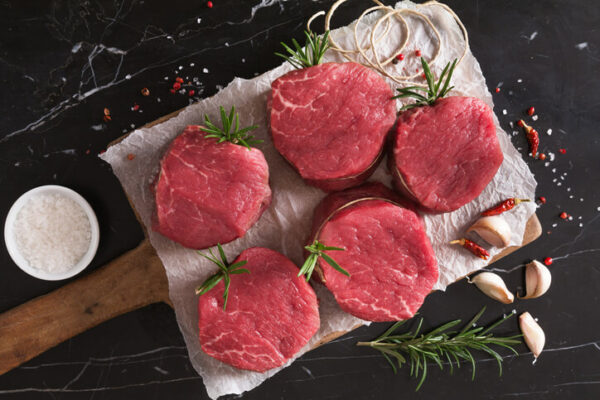 filet mignon steaks on a cutting board with salt and herbs