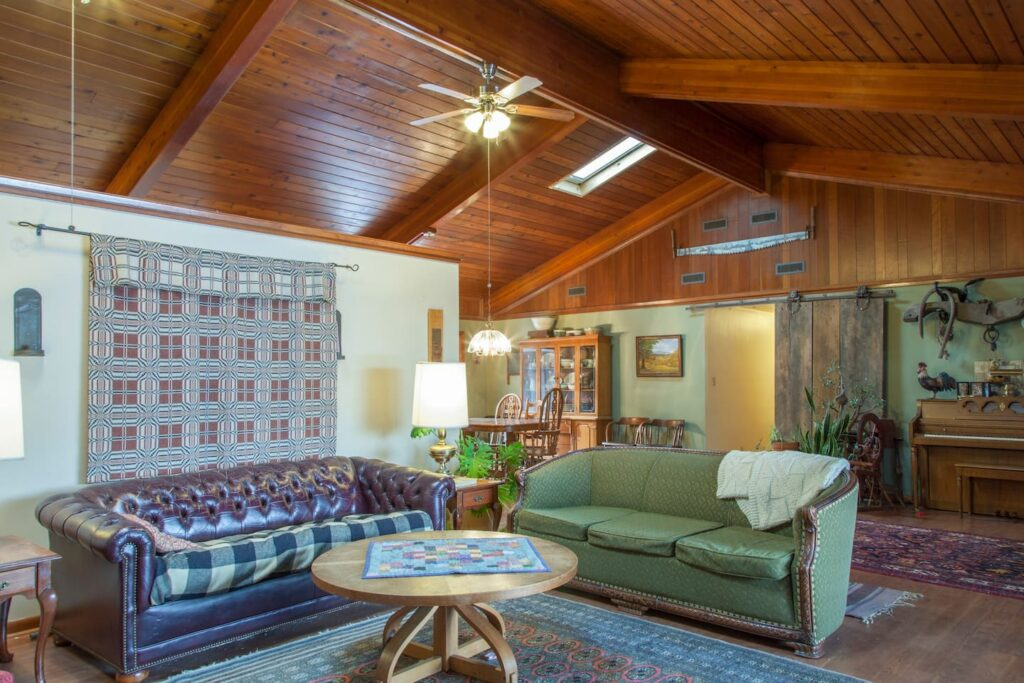 Inside of farm house, wood panel ceilings and cozy couches.